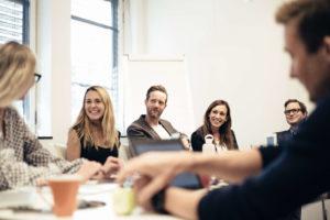 Smilende mennesker rundt møtebord - et kjent syn som senior kundeansvarlig i Starcom