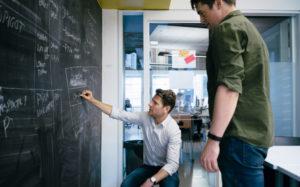 To ansatte foran tavlevegg. Som prosjektleder digital markedsføring vil du være med på mange spennende utviklingsprosjekter