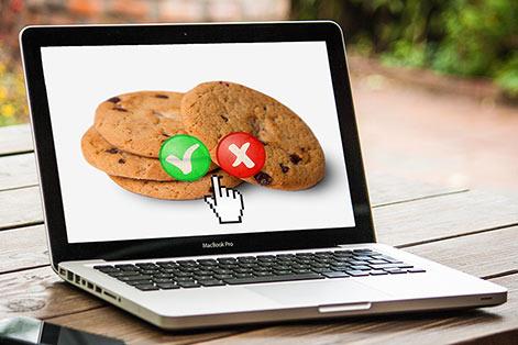 Laptop skjerm med bilde av cookies, med grønn hake og rødt kryss over. Hva betyr Googles utsettelse av cookie-bortfallet for annonsører?